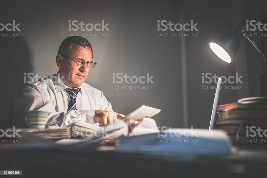 Senior man working after hours stock photo