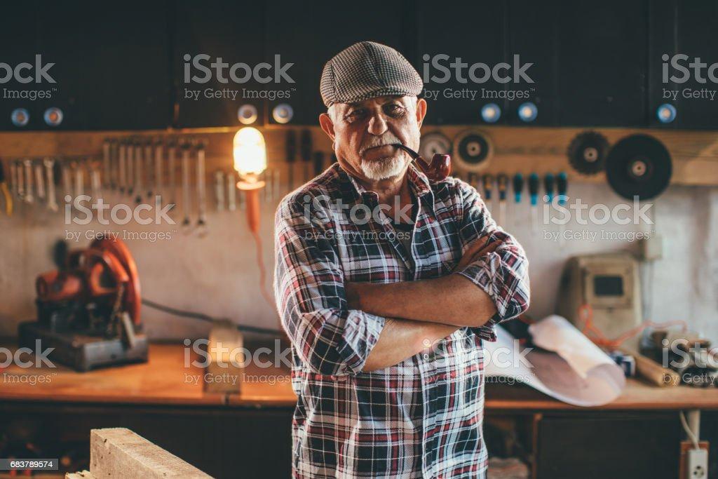 Senior Man Working in Workshop stock photo
