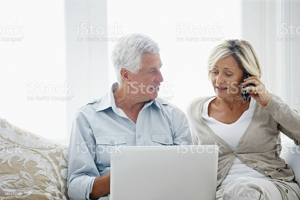 Senior man working on a laptop while lady using cellphone royalty-free stock photo