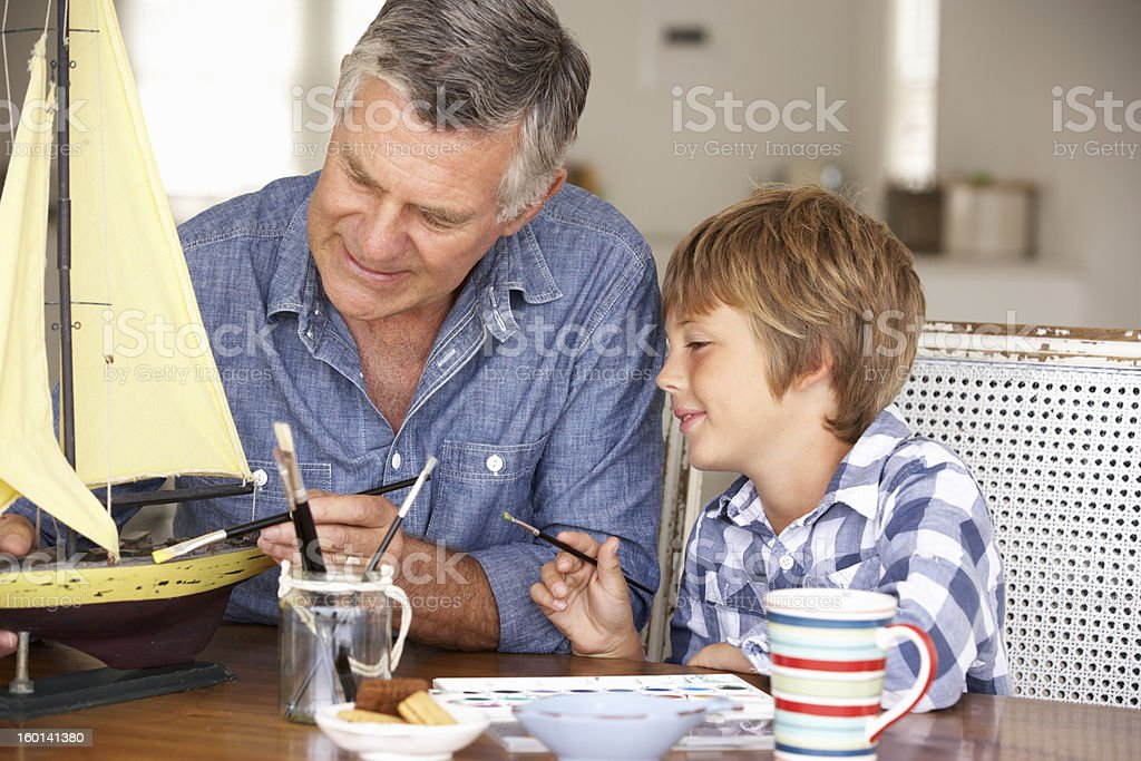 A senior man working on a model boat with his grandson  stock photo
