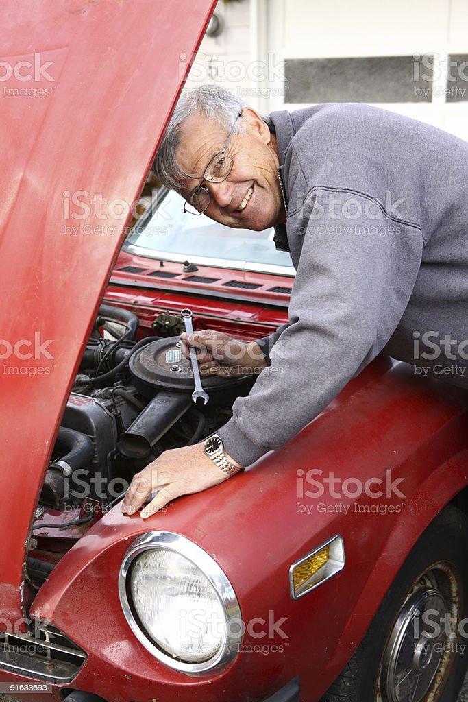 Senior man working on classic car royalty-free stock photo