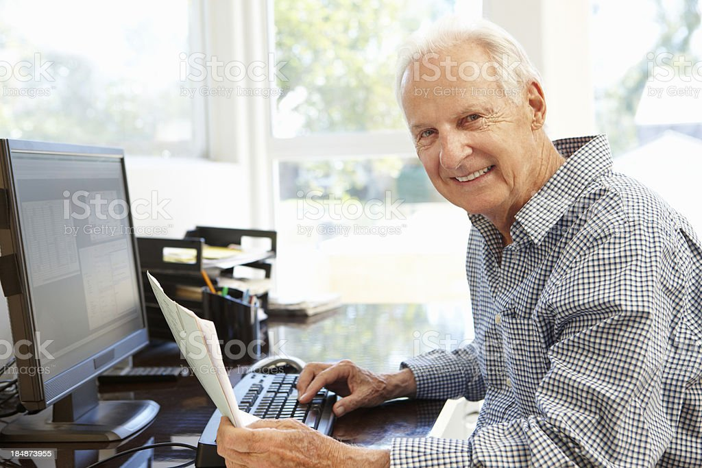 Senior man working on computer at home royalty-free stock photo