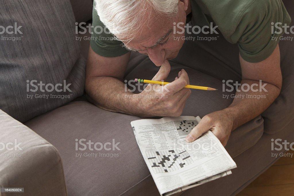 Senior man working on crossword puzzle stock photo