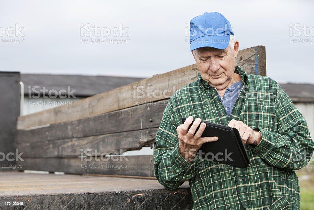Senior man working on farm with digital tablet stock photo