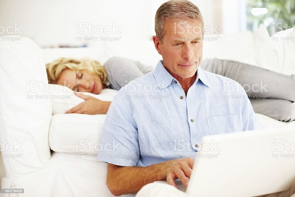 Senior man working on laptop with woman sleeping in background royalty-free stock photo