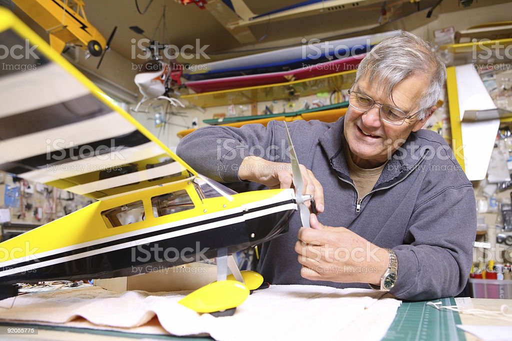 Senior man working on model airplane stock photo