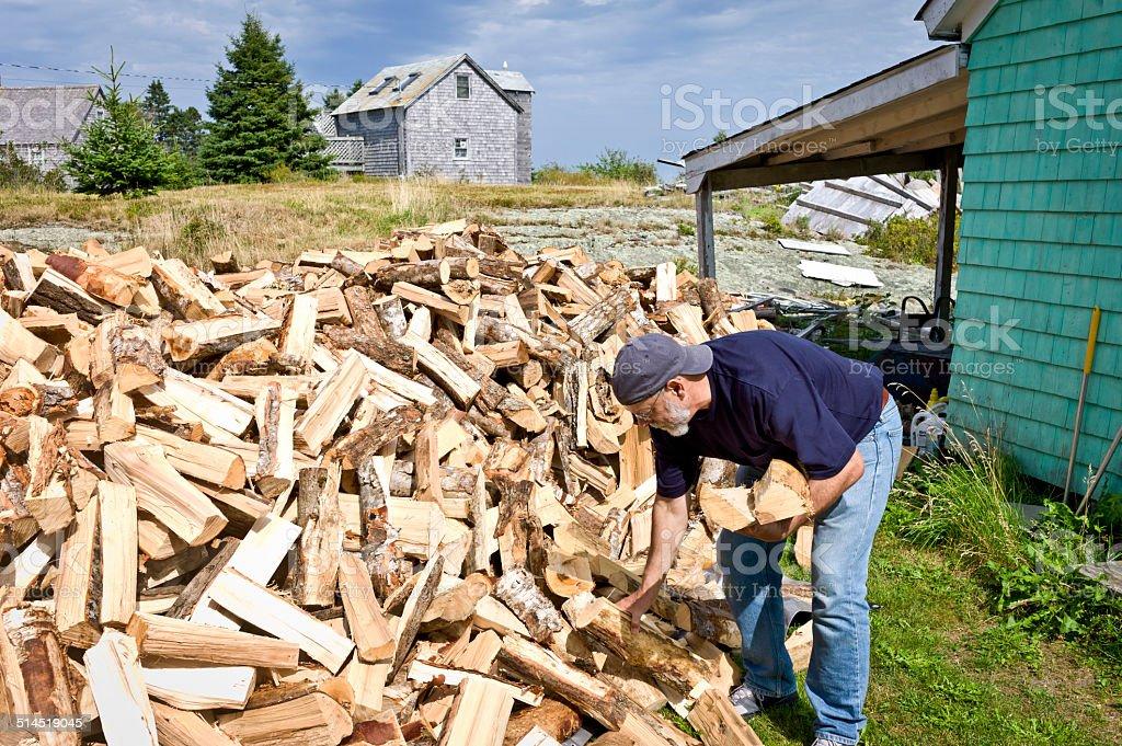 Senior Man Working Piling Firewood stock photo