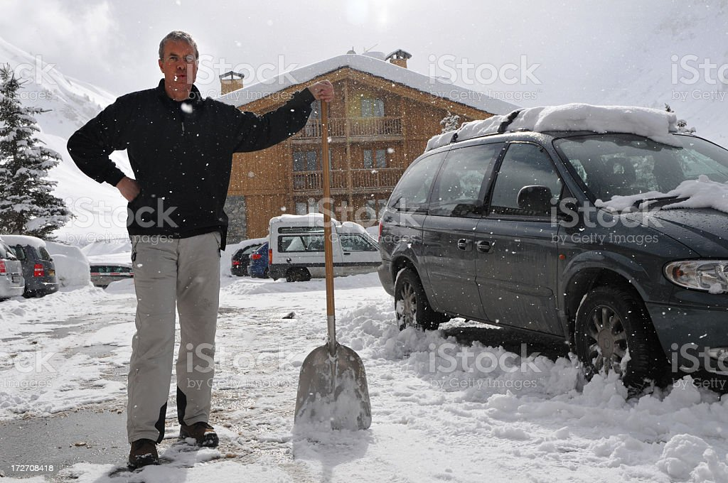 Senior man working  resting in the snow with shovel royalty-free stock photo
