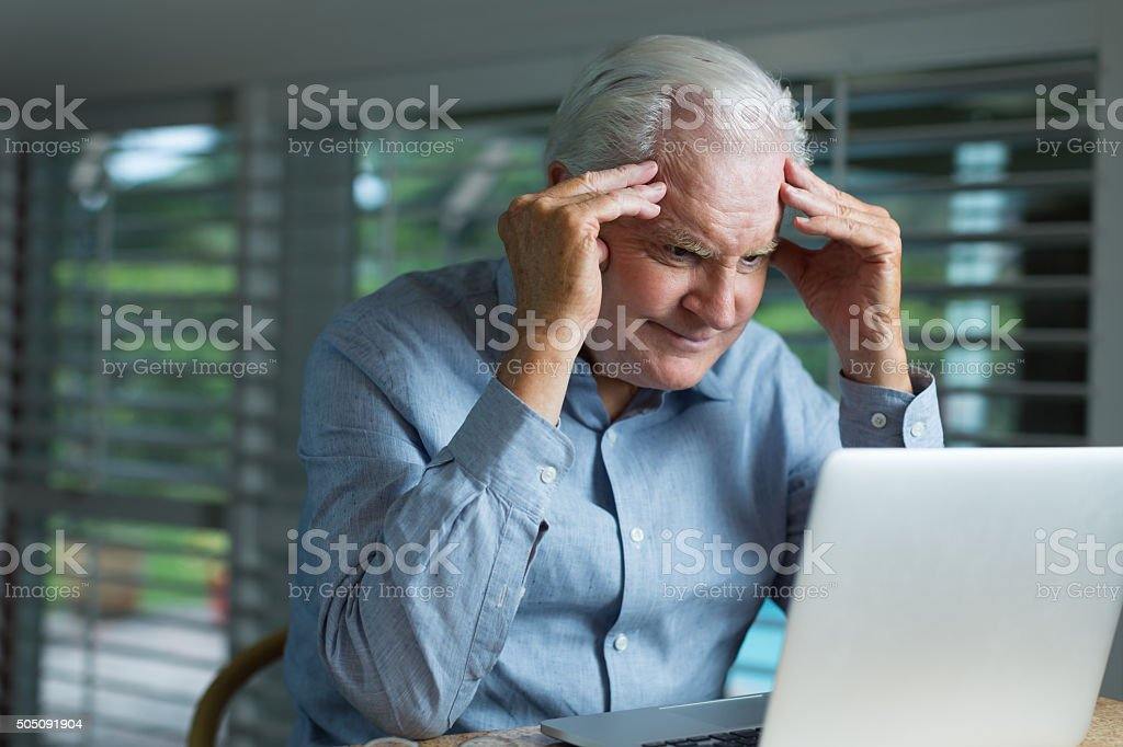 Senior man working with laptop stock photo