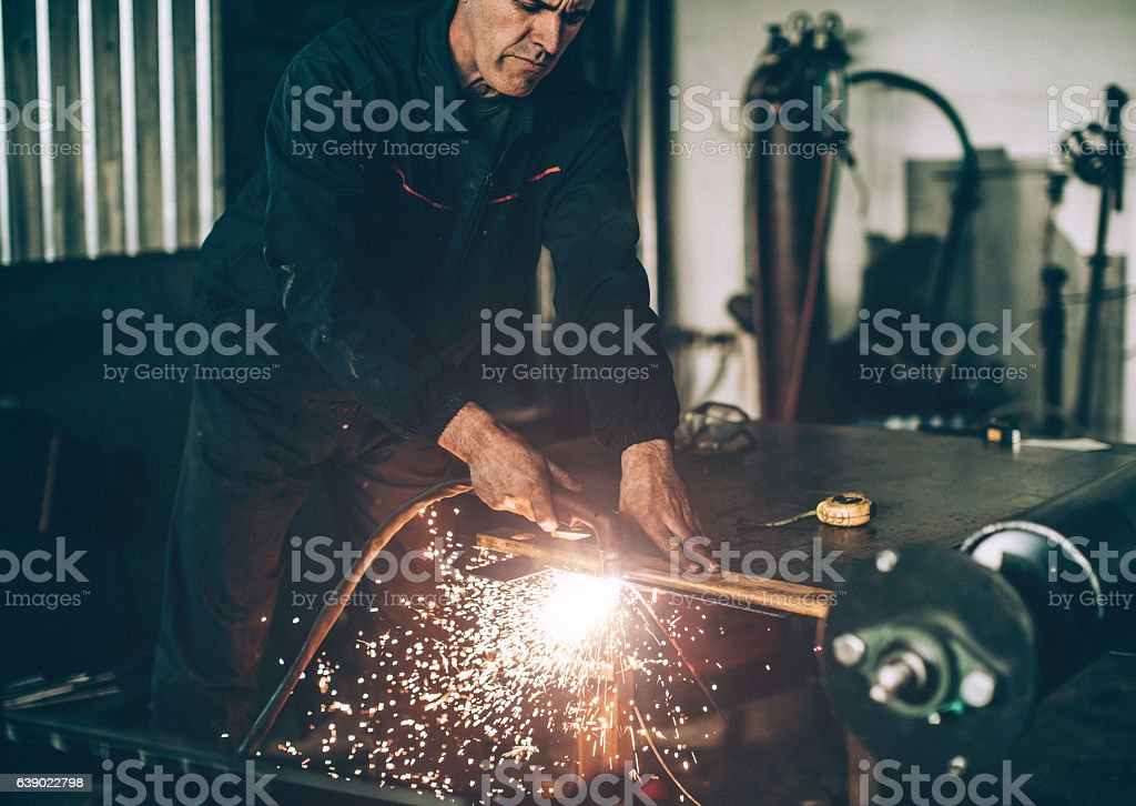 Senior man working with plasma cutter on steel plate... stock photo