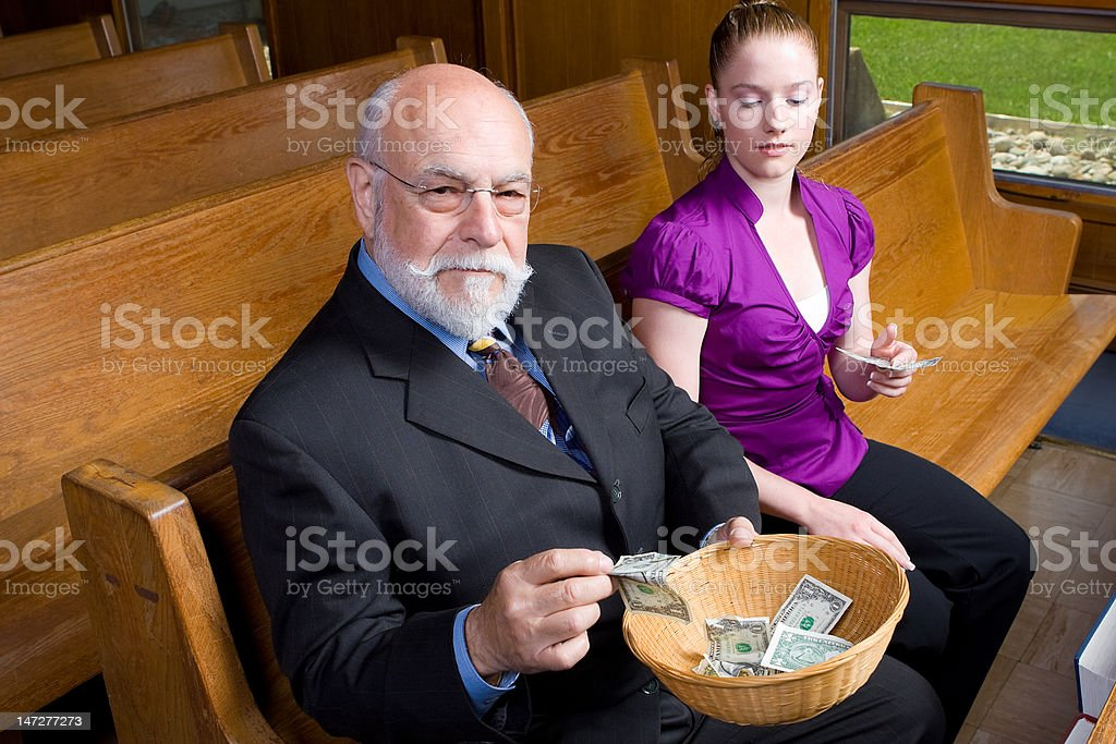 Senior Man Young Woman Putting Money into Church Offering Basket stock photo