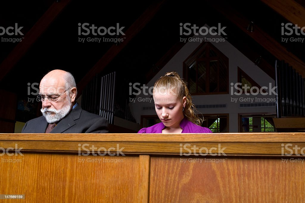 Senior Man Young Woman Sitting Head Bowed Praying Church Pew royalty-free stock photo