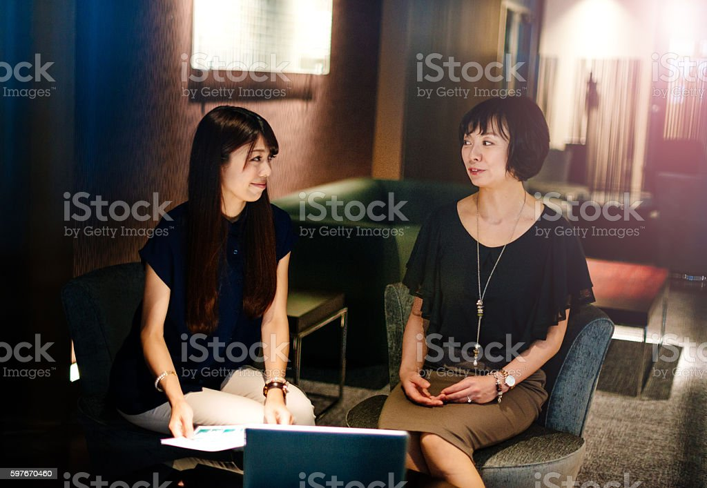 Senior manager gives advice to junior colleague in Japan stock photo