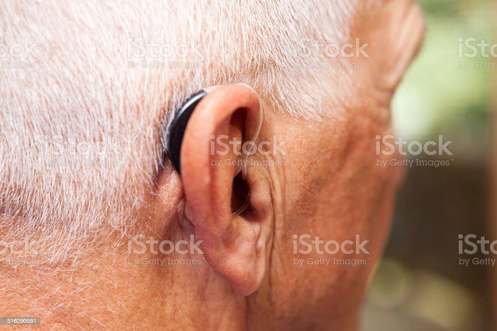 Senior Man's Ear with Hearing Aid stock photo