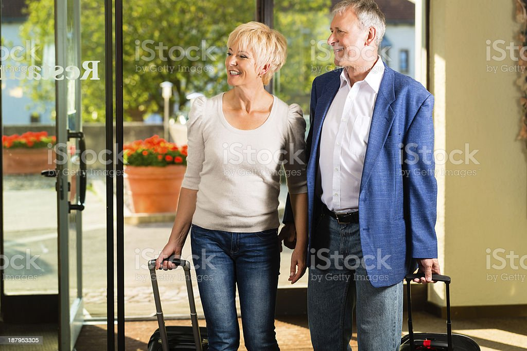 Senior married couple arriving at Hotel stock photo