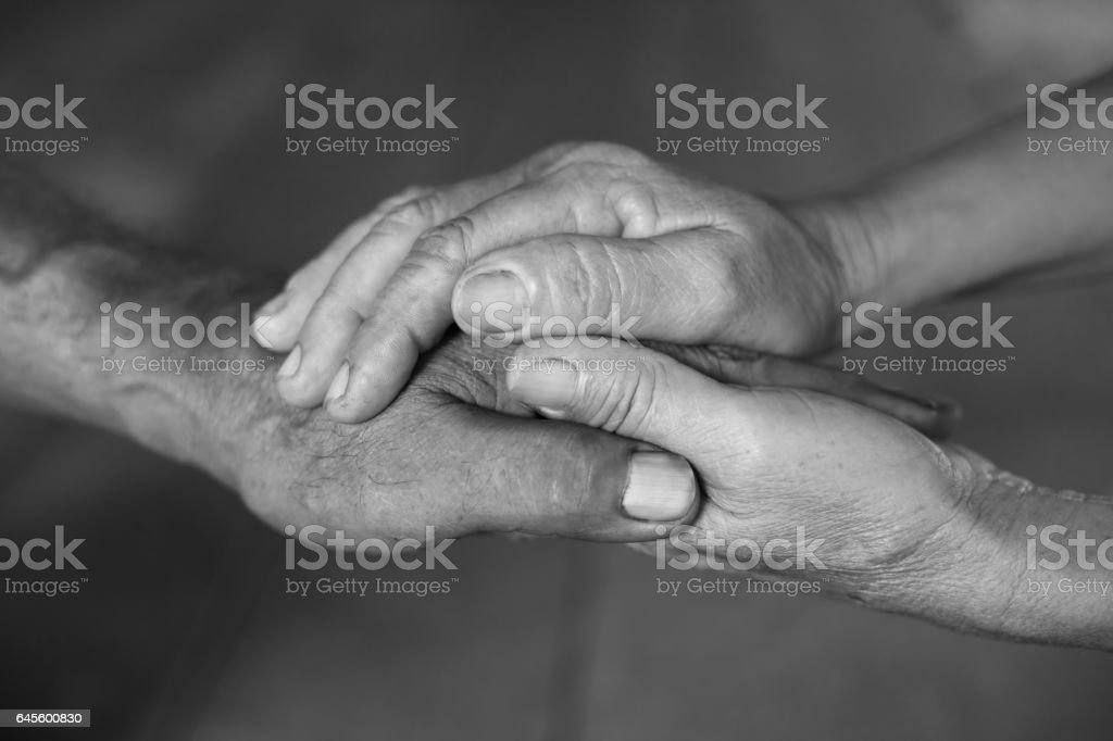 Senior married couple holding hands stock photo