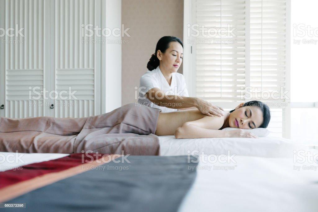 Senior massage therapist making oil massage to a young woman stock photo