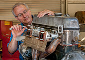 Senior Mechanic Tearing Down an Old Car Motor
