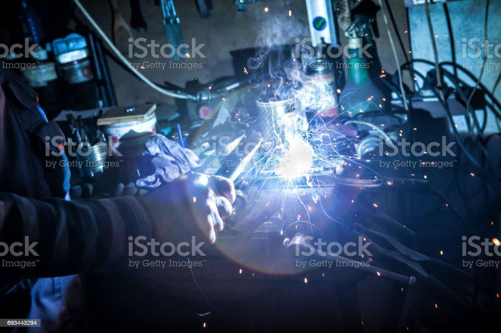 Senior caucasian mechanic in his factory welding metal part of bicycle