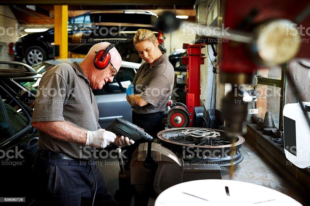 Senior mechanic working on car rims in garage stock photo
