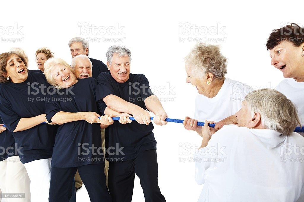 Senior men and women playing tug of war royalty-free stock photo