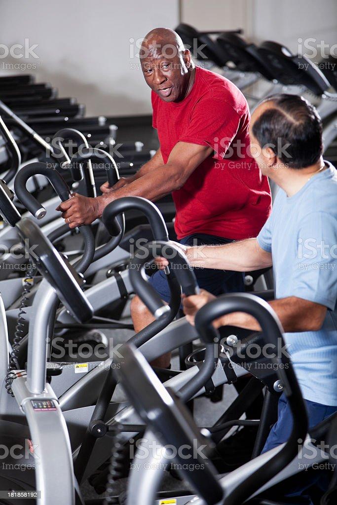 Senior men at health club on elliptical trainers stock photo