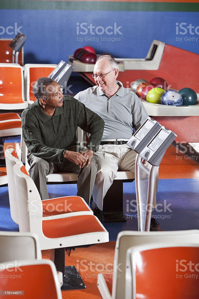 Senior men chatting in bowling alley royalty-free stock photo