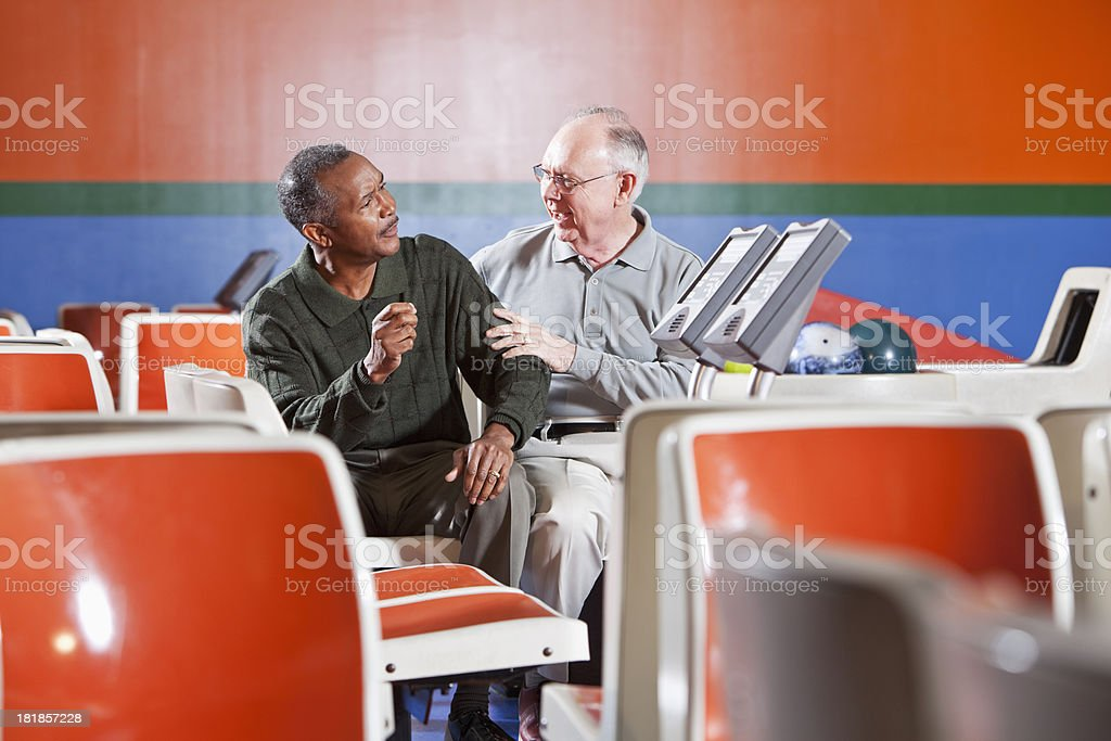 Senior men chatting in bowling alley stock photo