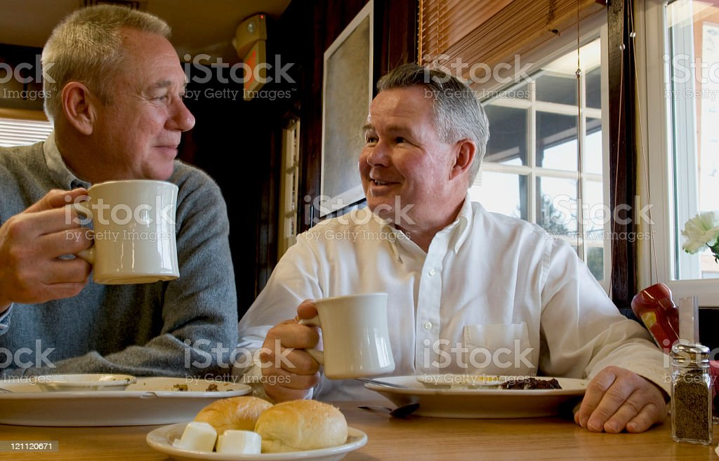 Senior Men Eating and Drinking Coffee stock photo