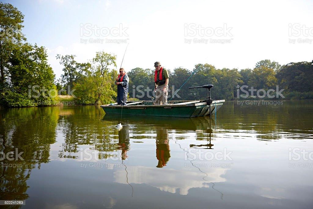 Senior men fishing together on lake stock photo