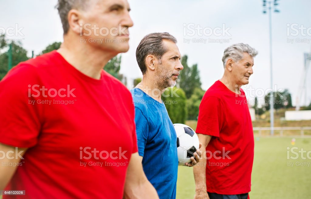 Senior men in red and blue jersey standing on the soccer field with...