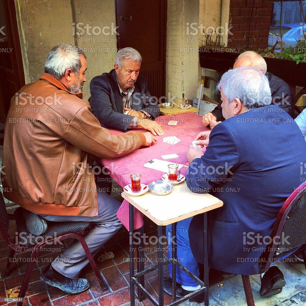 Senior Men playing cards and drinking Turkish tea outdoors stock photo