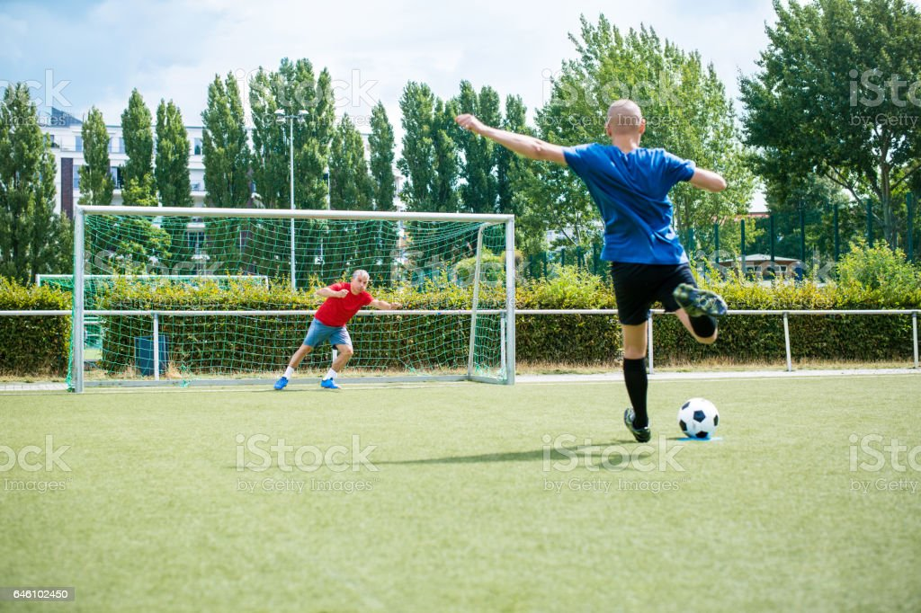 Senior men playing soccer on the field stock photo