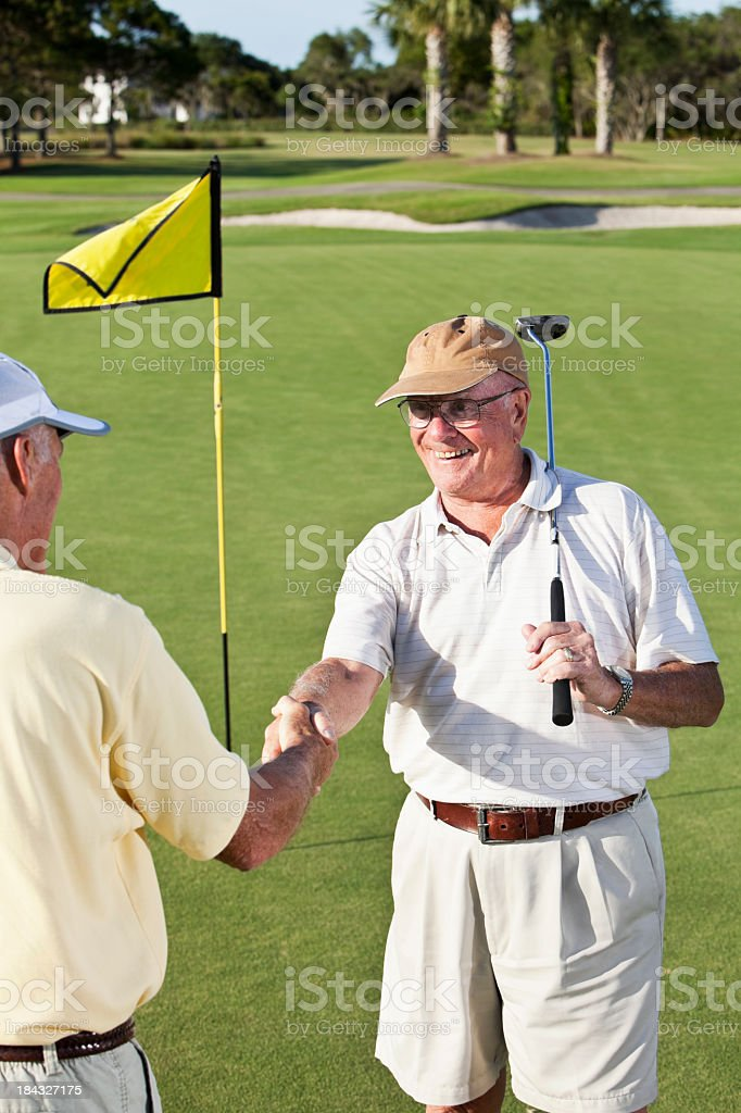 Senior men shaking hands on golf course royalty-free stock photo