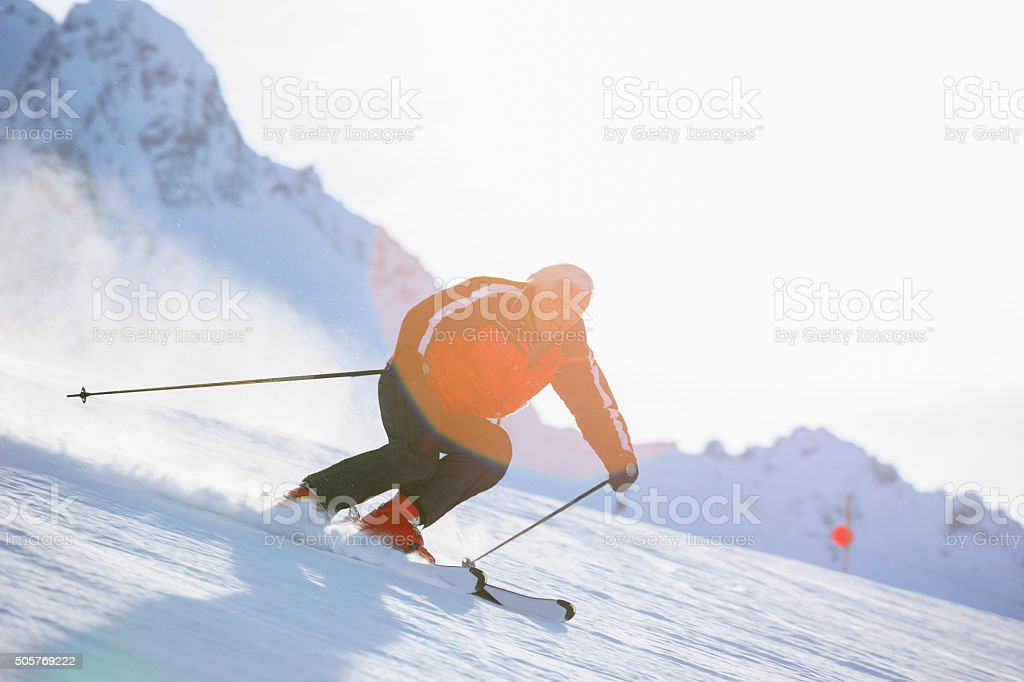 Senior men snow skier skiing on sunny ski resorts stock photo