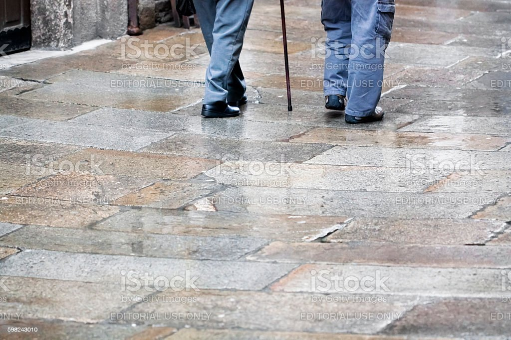 Senior men walking, rainy day, walking cane. stock photo