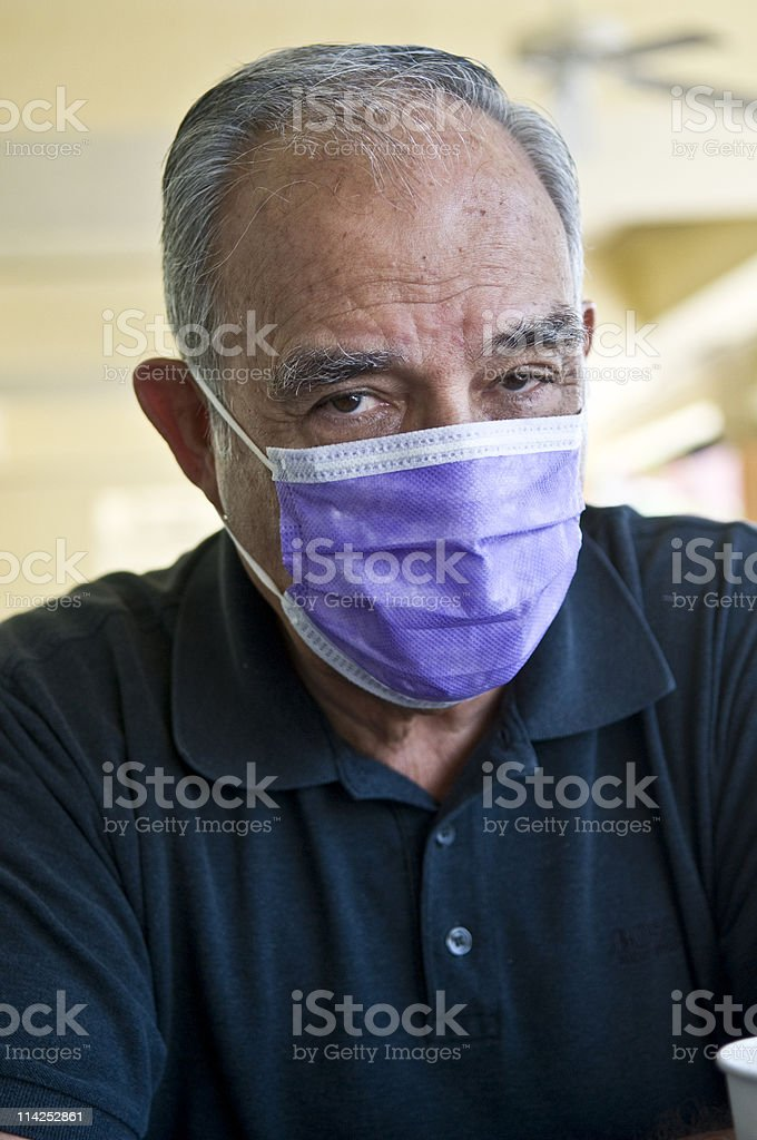 Senior mexican wearing a flu mask stock photo