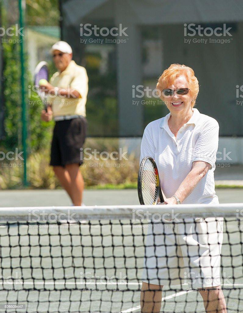 Senior mixed doubles tennis match stock photo