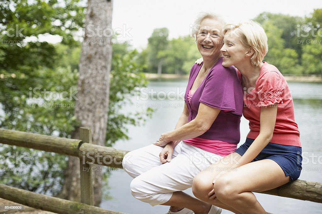 Senior mother and daughter sitting near pond royalty-free stock photo
