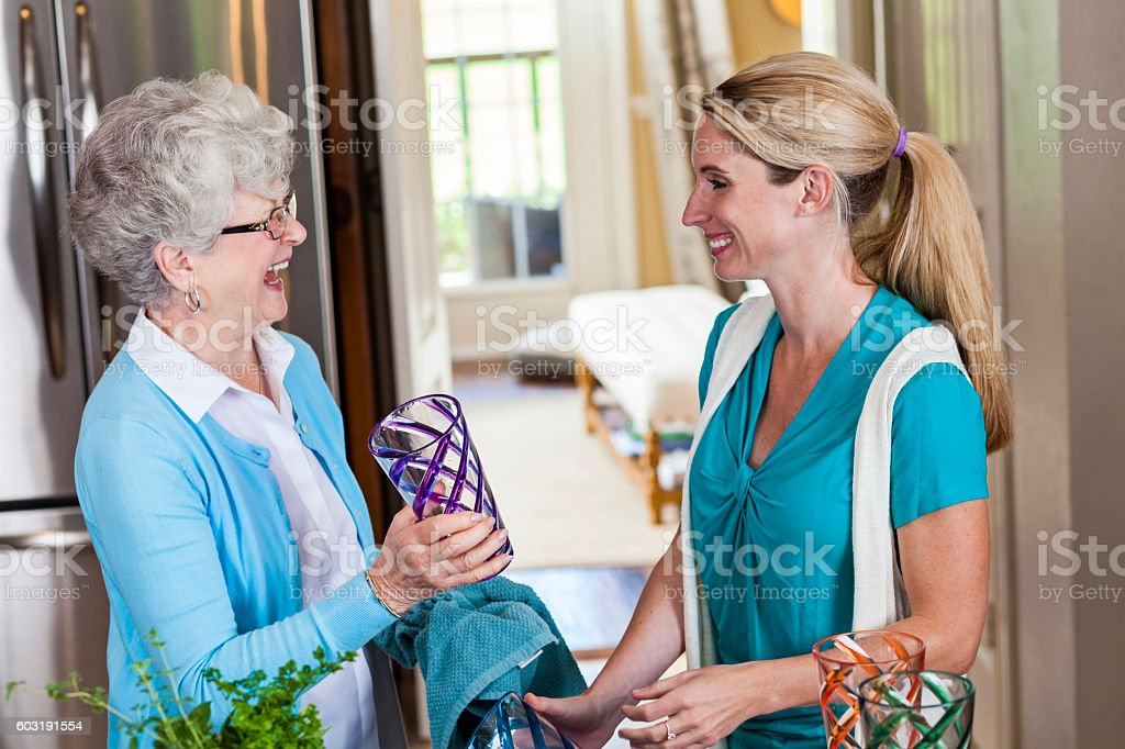 Senior mother and her daughter wash dishes after dinner stock photo