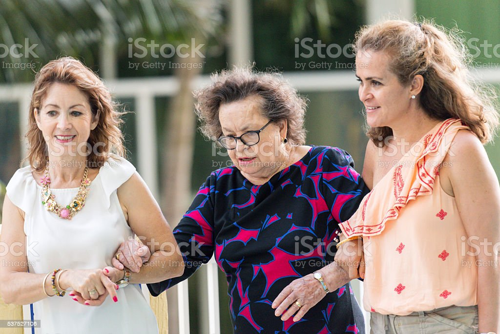 Senior mother being helped to walk by her mature daughters stock photo