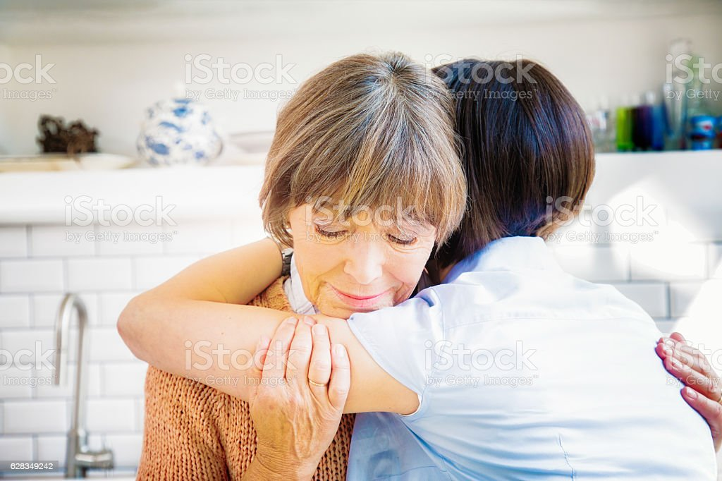 Senior mother hugs daughter while grieving stock photo