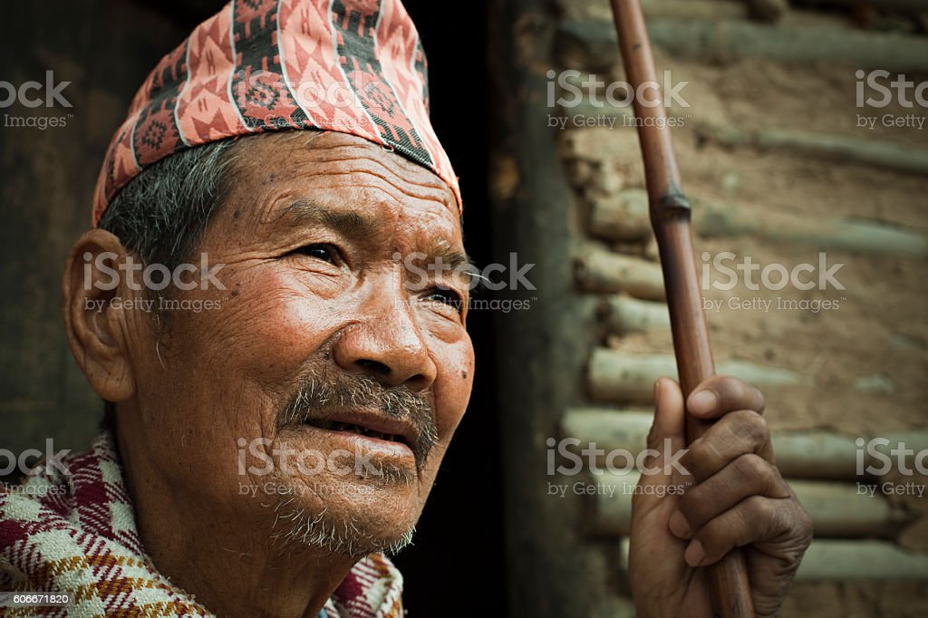 Senior Nepalese peasant man with stick near adobe house. stock photo