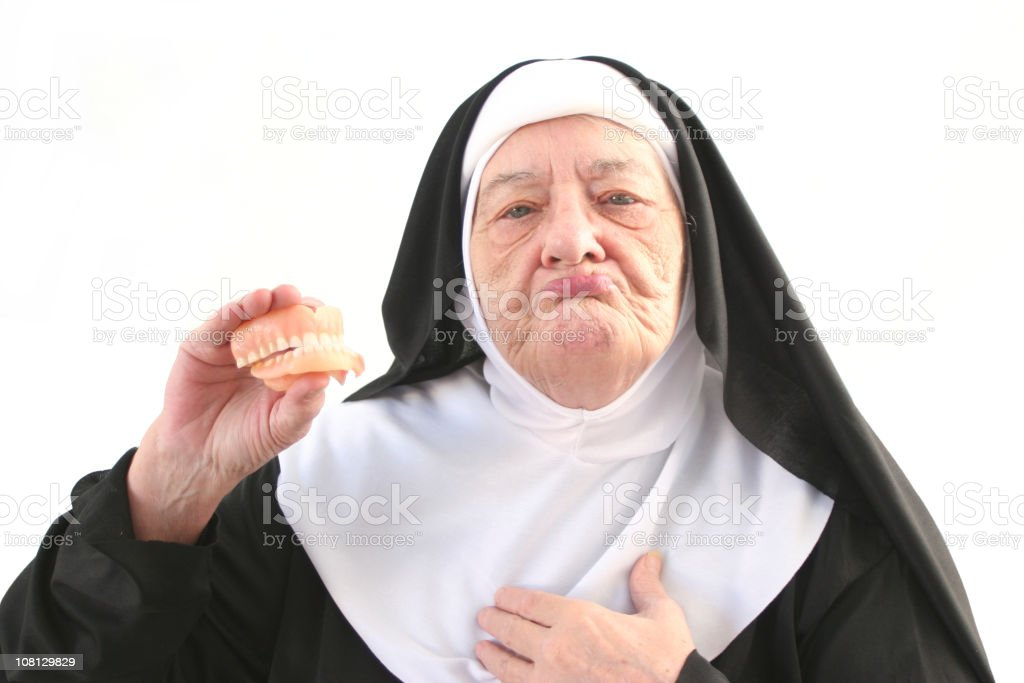 Senior Nun Holding Up Dentures, Isolated on White stock photo