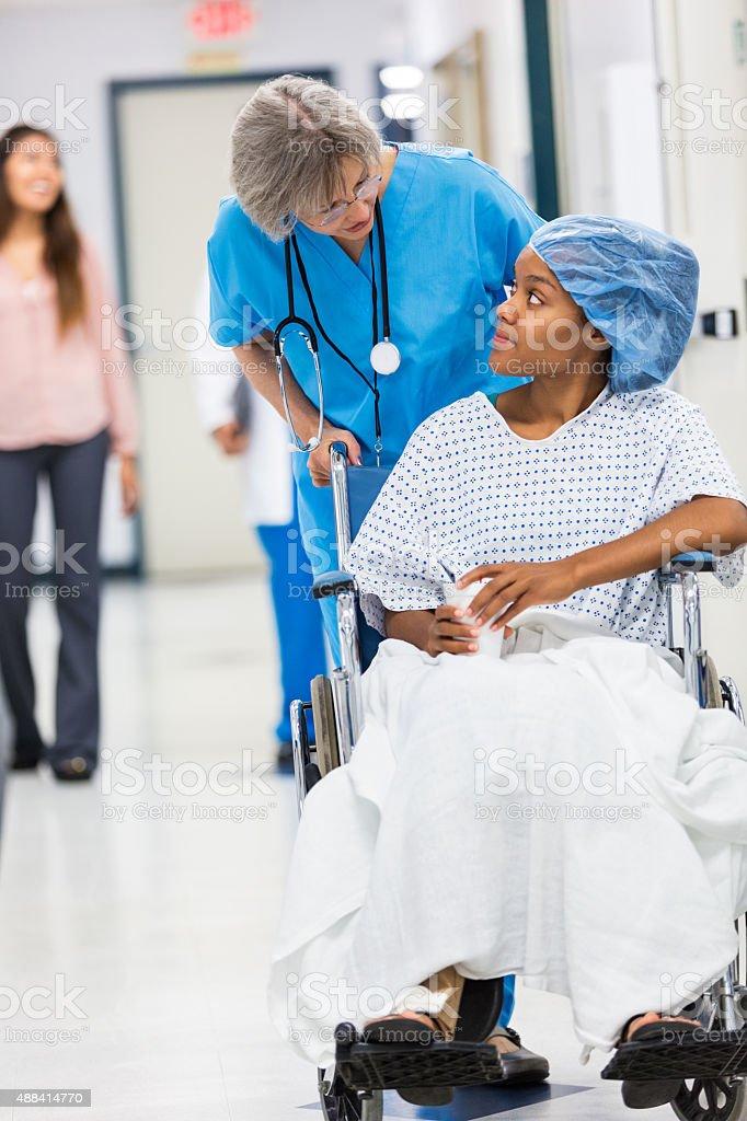 Senior nurse pushing patient's wheelchair in hospital hallway stock photo