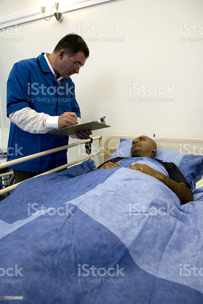 Senior nurse visiting a patient in a hospital ward royalty-free stock photo
