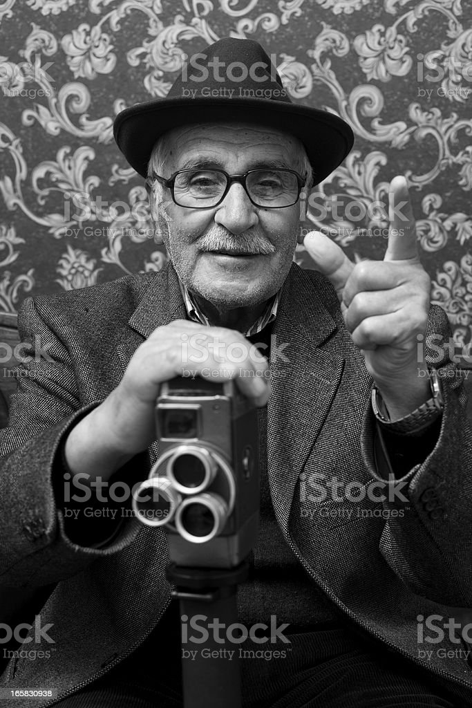 Senior old style videographer posing with his video camera stock photo