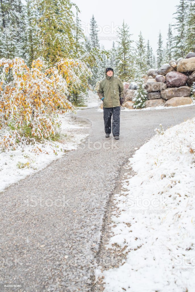 Senior on vacation in falling snow stock photo