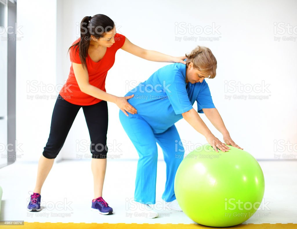 Senior overweight woman exercising in a gym. stock photo