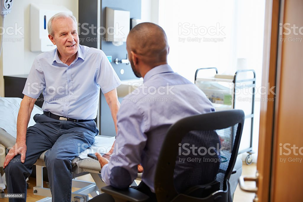 Senior Patient And Doctor Have Consultation In Hospital Room stock photo